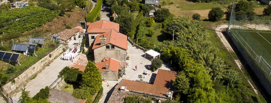 La casa rodeada de su patio en piedra